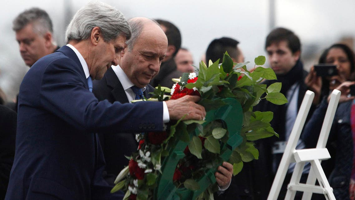 U.S. Secretary of State John Kerry, left, and French Foreign Minister Laurent Fabius lay flowers Friday, Jan. 16, 2015, at the site of a kosher market where four hostages were killed in a terrorist attack last week in Paris, France. AP