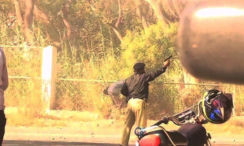 کراچی میں طلبہ کے احتجاجی مظاہرے کے دوران ایک پولیس اہلکار فائرنگ کرتے ہوئے۔
