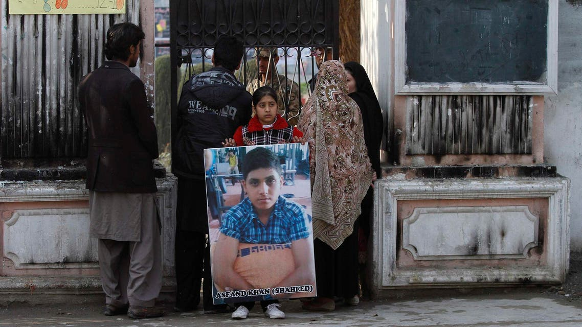 The sister of a student who was killed during an attack by Pakistan's Taliban gunmen carries his portrait while standing with her family members, in Peshawar January 14, 2015. (Reuters)