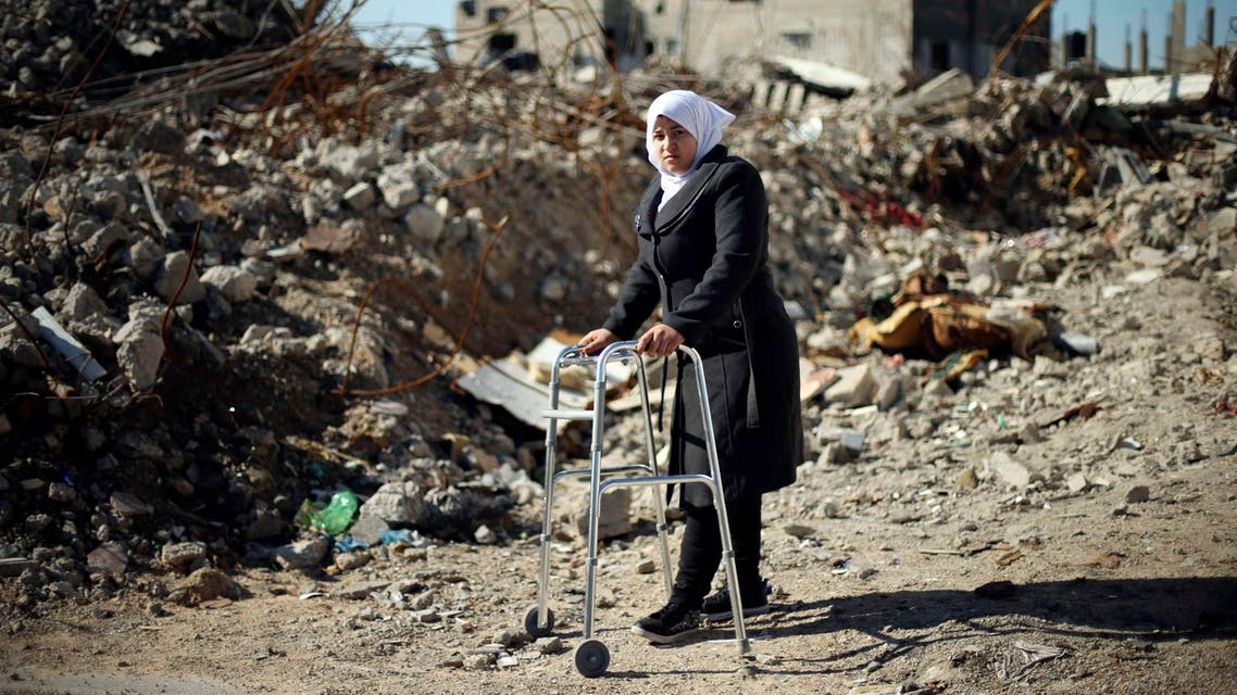 Palestinian girl Manar Al-Shinbari, 15, who lost her both legs by what medics said was Israeli shelling at a UN-run school where she was taking refuge during the 50-day war last summer, uses her walker near the ruins of her house that witnesses said was destroyed by Israeli shelling during the war, in Biet Hanoun in the northern Gaza Strip January 13, 2015. Reuters