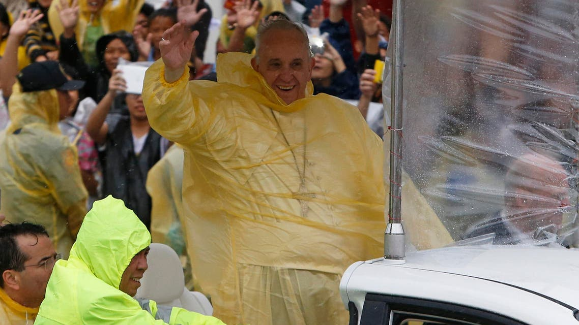 Pope Francis smiles as he waves to residents during a motorcade in Tacloban city, after holding a mass near the airport, January 17, 2015. Reuters