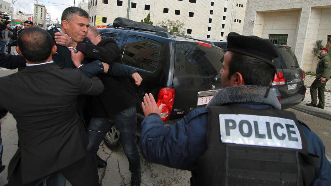 Members of Palestinian security forces and a policeman hold back a protester after eggs were thrown at Canada's Foreign Minister John Baird, during his visit to the West Bank city of Ramallah, January 18, 2015. (Reuters)