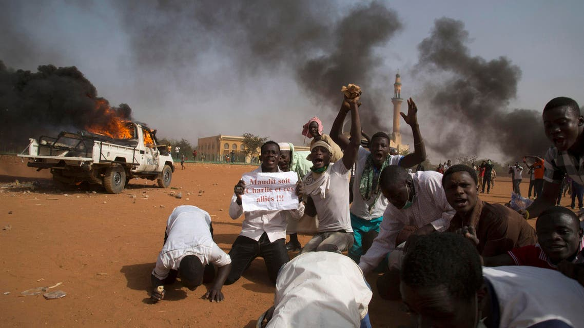 A man (2nd L) holds a sign reading Charlie and his Allies are Damned during a protest in Niger. (Reuters)