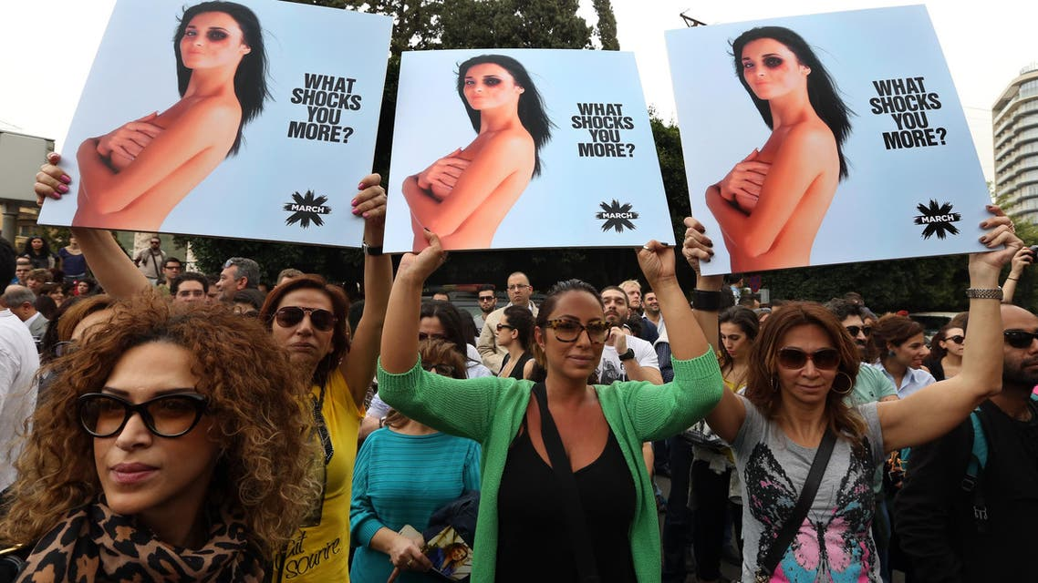 Lebanese women hold posters to mark International Woman's Day during a rally of thousands demanding that parliament approves a law that protects women from domestic violence, in Beirut, Lebanon, Saturday, March. 8, 2014. (AFP)