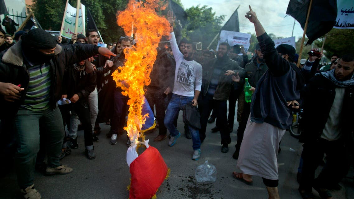 Palestinian Salafists, members of an ultraconservative sect of Islam, burn a French flag and chant angry slogans during a protest against caricatures of the Prophet Muhammad published in the satirical French weekly magazine Charlie Hebdo, outside the French Cultural Center in Gaza City, Monday, Jan. 19, 2015. (AP Photo)