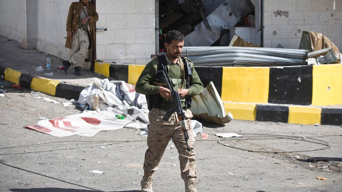 Houthi Shiite Yemeni wearing an army uniform stand guard in front of a building damaged during recent clashes near the presidential palace in Sanaa, Yemen, Tuesday, Jan. 20, 2015. AP