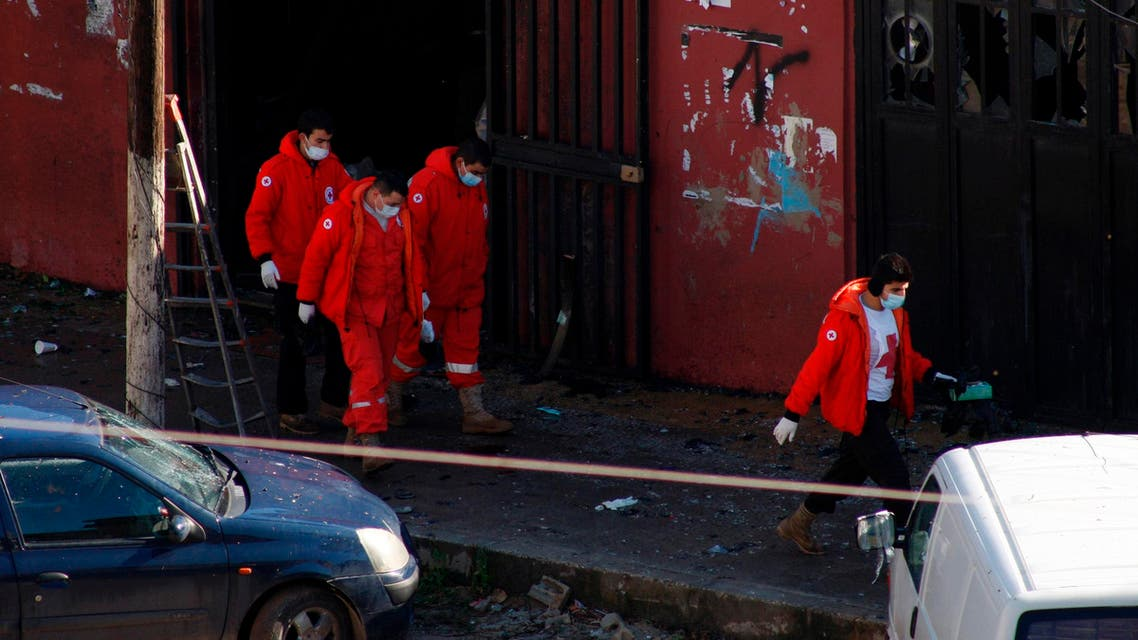 Red Cross members inspect a cafe where a suicide bomb attack took place in Jabal Mohsen, Tripoli