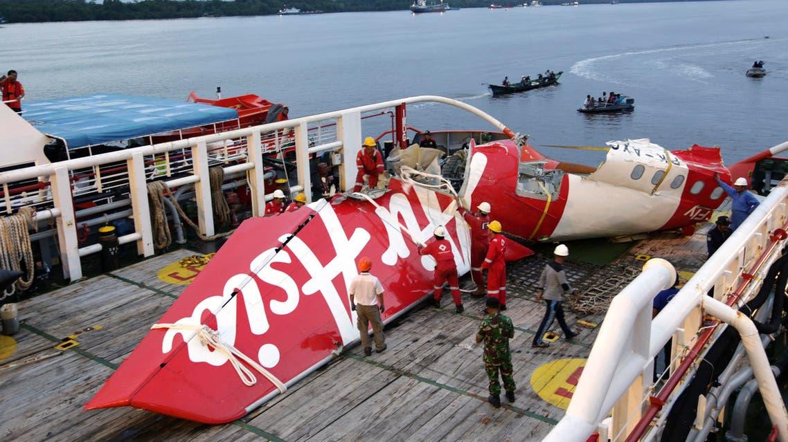 Crew members of Crest Onyx ship prepare to unload parts of AirAsia Flight 8501 from a ship at Kumai port in Pangkalan Bun,Sunday, Jan.11, 2015. AP