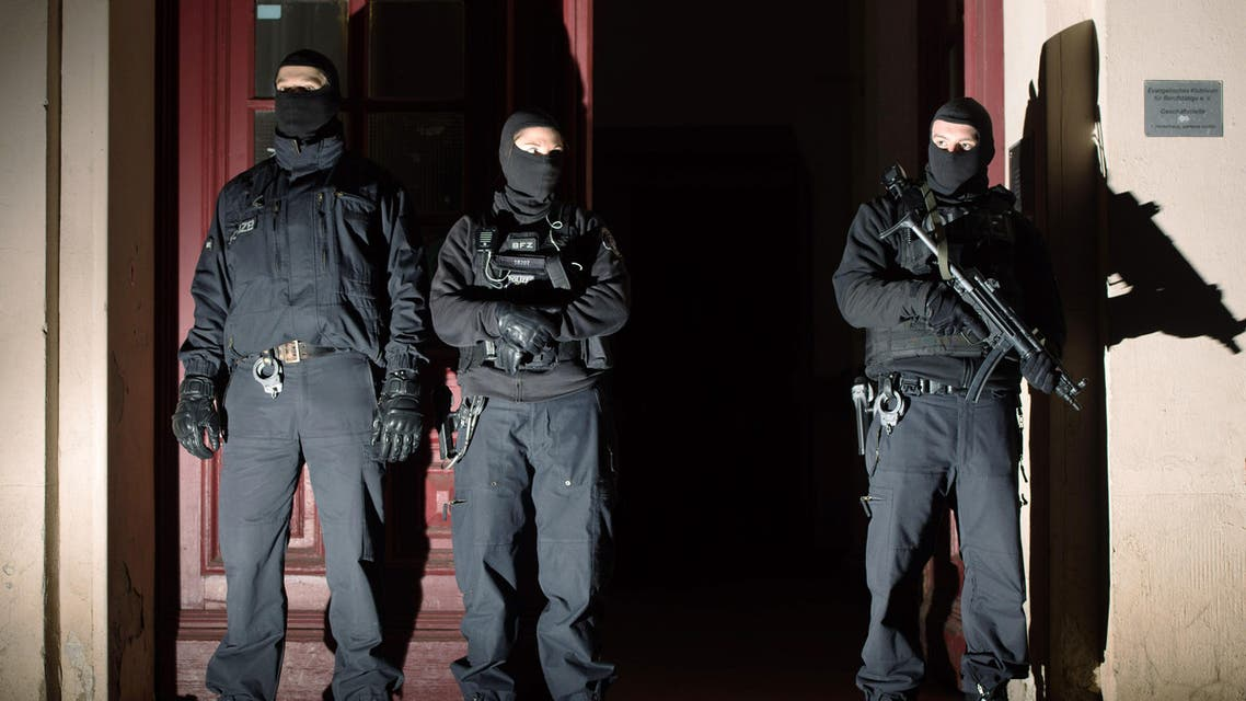 Special police force guards the entrance of a house in Berlin as police raids several residences in Berlin on suspicion of recruiting fighters and procuring equipment and funding for the so-called Islamic State terrorism group in Syria Friday morning Jan 16, 2015. (AP Photo)