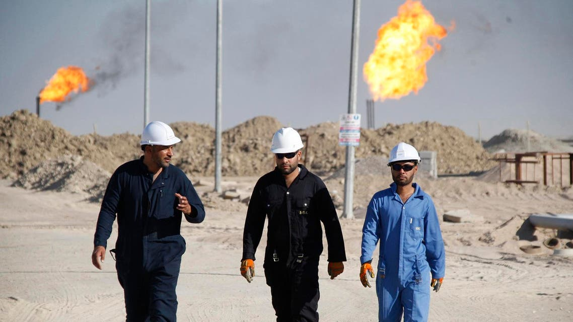 Iraqi workers walk in West Qurna oilfield in Iraq's southern province of Basra, in this file photo taken Nov. 28, 2010.  (Reuters)