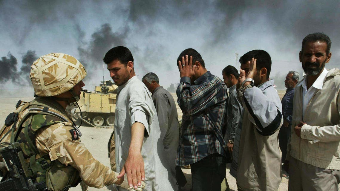 British soldiers check Iraqi men on the outskirts of Basra who are fleeing from this southern Iraqi town Tuesday, April 01, 2003. (AP Photo)