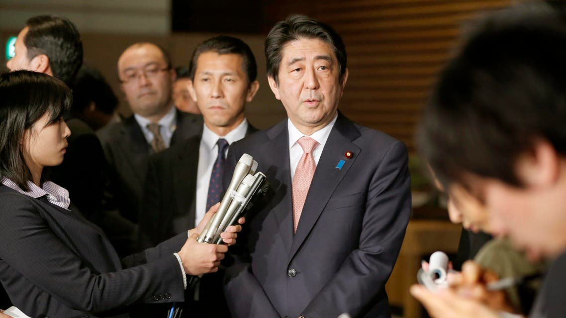 Japan's Prime Minister Shinzo Abe, center, speaks to reporters at the prime minister's official residence in Tokyo, Wednesday, Jan. 21, 2015, shortly after returning from his six-day Middle East tour. AP