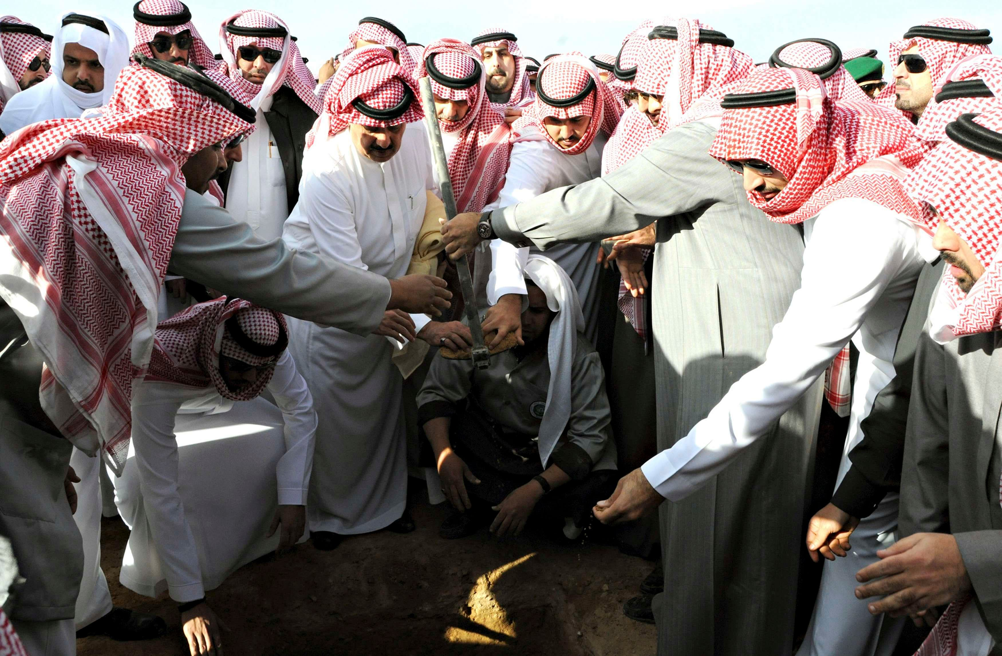 Mourners bury the body of Saudi King Abdullah during his funeral in Riyadh January 23, 2015, in this handout photo provided by Saudi Press Agency. (Reuters)