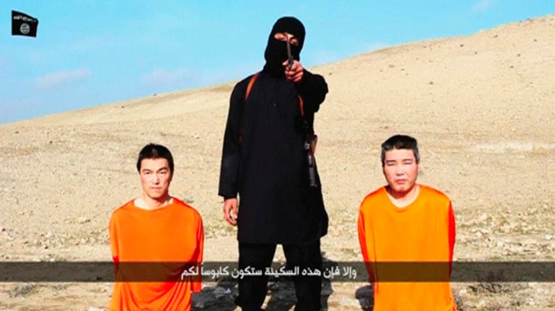 A masked person holding a knife speaks as he stands in between two kneeling men in this still image taken from an online video released by the militant Islamic State group on January 20, 2015. (Reuters)