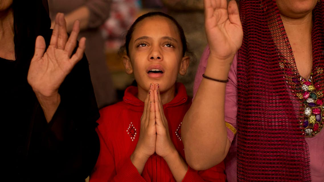 In this Thursday, Nov. 8, 2012 picture, a Coptic girl prays during a mass at the Cave Cathedral or St. Sama'ans Church in the Moqattam area, Cairo, Egypt. Egypt's Christian minority, about 10 percent of the population of more than 80 million, has long complained of discrimination. AP