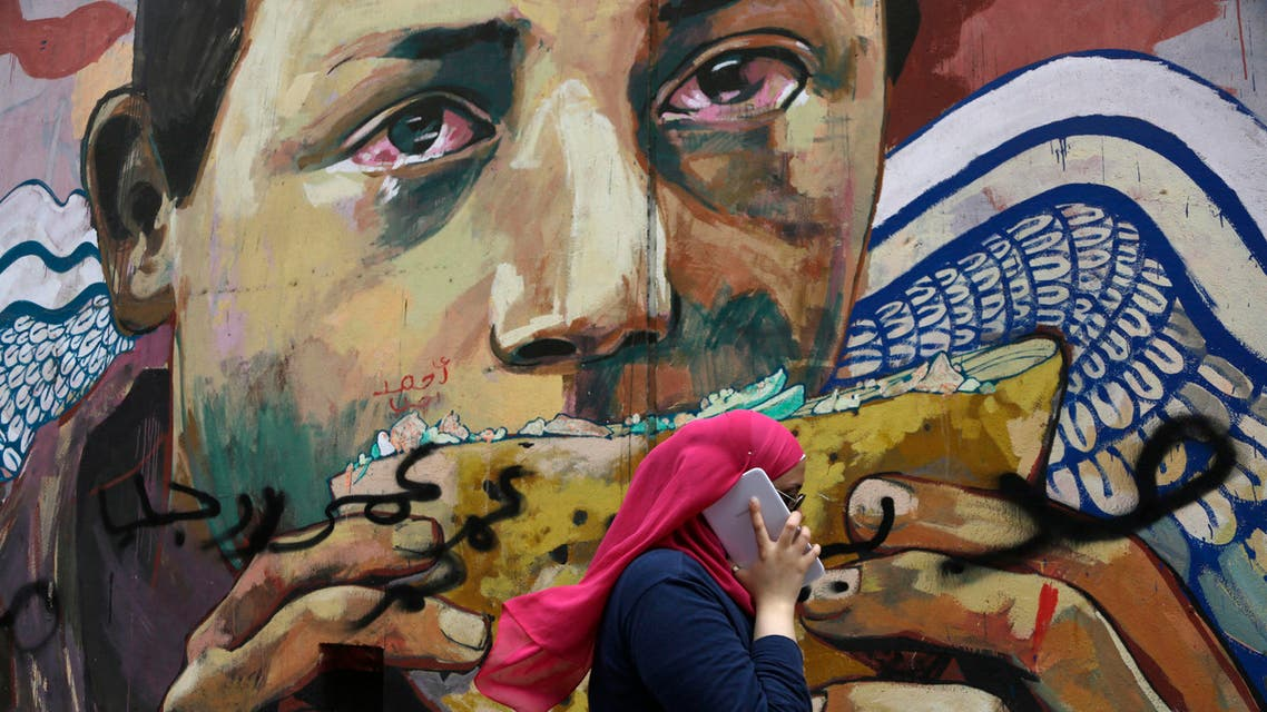 A woman talks on her tablet phone while walking past graffiti in Mohammed Mahmoud Street near Tahrir Square, in downtown Cairo, Egypt, Wednesday, Sept. 17, 2014. AP