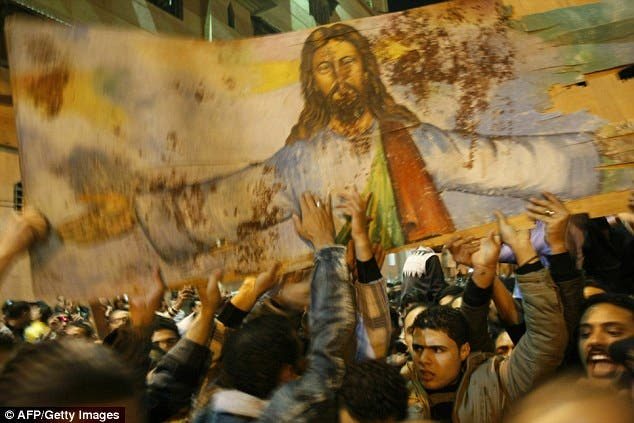 Spattered with blood: Christians carry a portrait of Christ taken from the bombed church of al-Qiddissian through the streets of Alexandria AFP