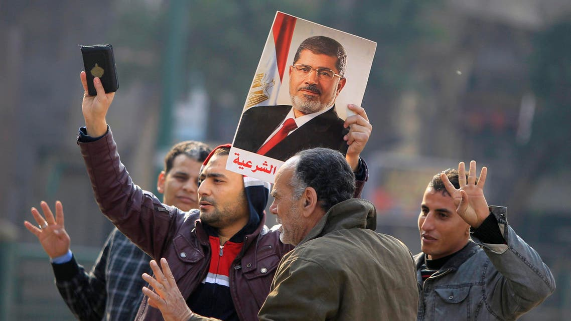 Supporters of the Muslim Brotherhood and ousted Egyptian President Mohamed Mursi hold a copy of the Koran and Mursi's picture at Talaat Harb Square, in Cairo, Jan. 25, 2015. (Reuters)