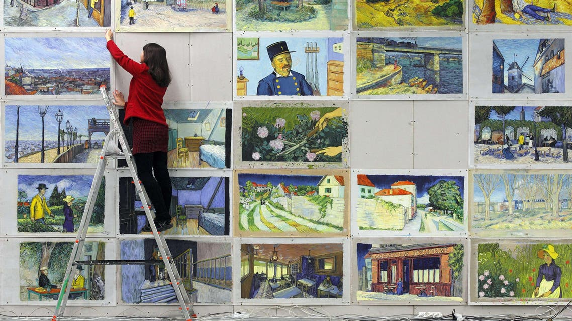 Joanna Maleszyk hangs up recreations of Vincent van Gogh paintings at a film studio in the northern Polish city of Gdansk on December 5, 2014. (AFP)