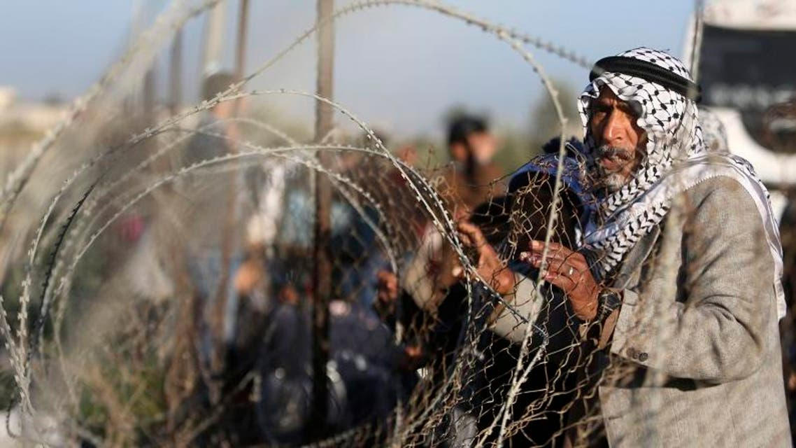 A Palestinian man, hoping to cross into Egypt, stands behind a fence as he waits for a travel permit at the Rafah crossing between Egypt and the southern Gaza Strip January 22, 2015. reuters