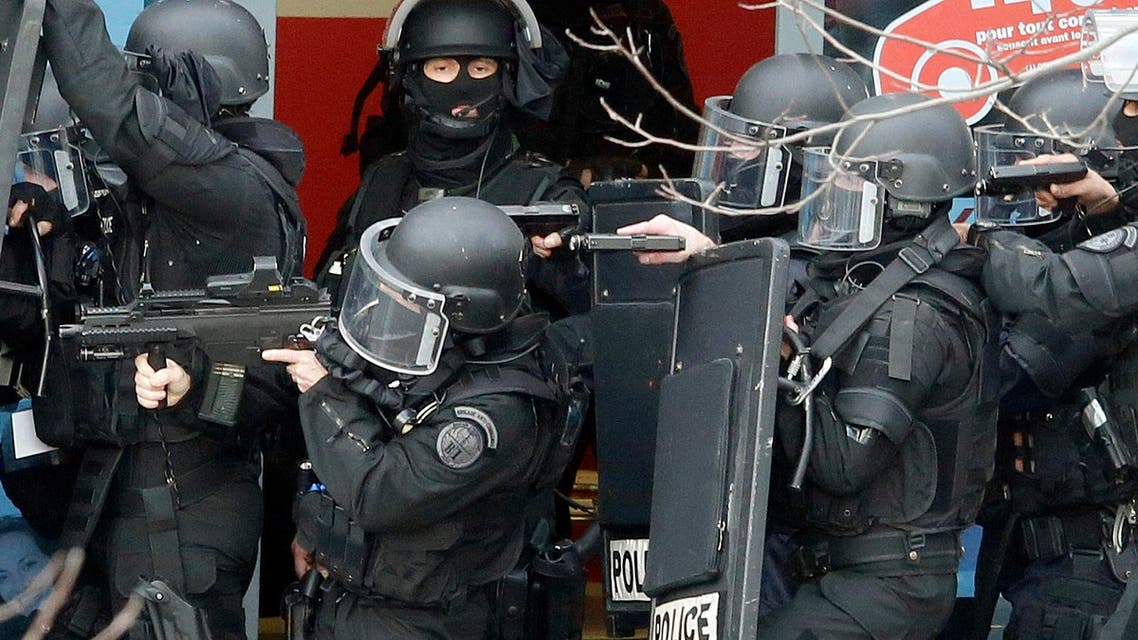 Members of special French RAID forces secure the area next to the post offices in Colombes outside Paris, were an armed gunman is holding hostages January 16, 2015. REUTERS