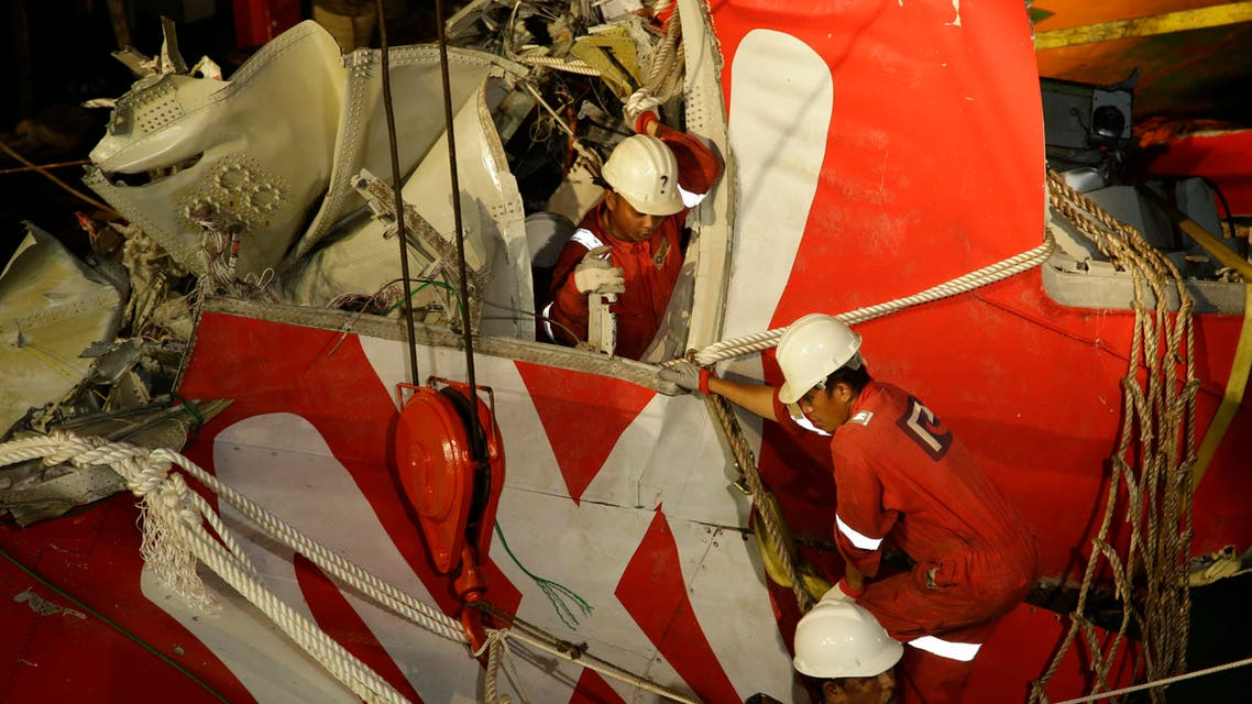 Crew members of Crest Onyx ship unload the wreckage of part of the ill-fated AirAsia Flight 8501 crashed off the Java Sea, at Kumai port in Pangkalan Bun, Indonesia, Sunday, Jan. 11, 2015. AP