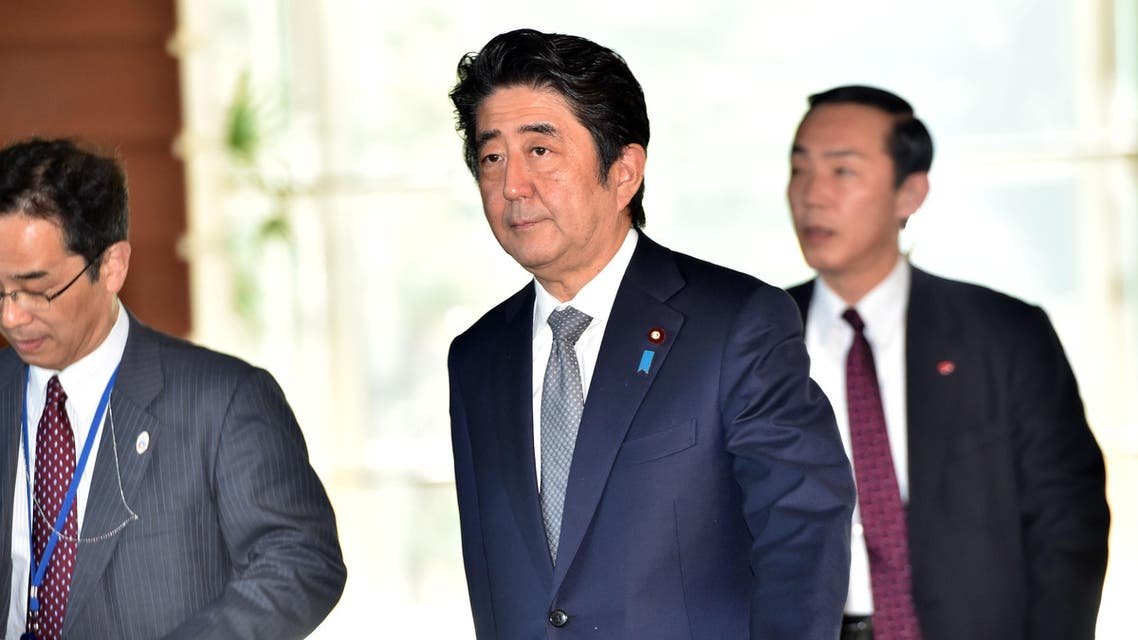 Japanese Prime Minister Shinzo Abe (C) walks at his official residence in Tokyo after a cabinet meeting on January 27, 2015. AFP