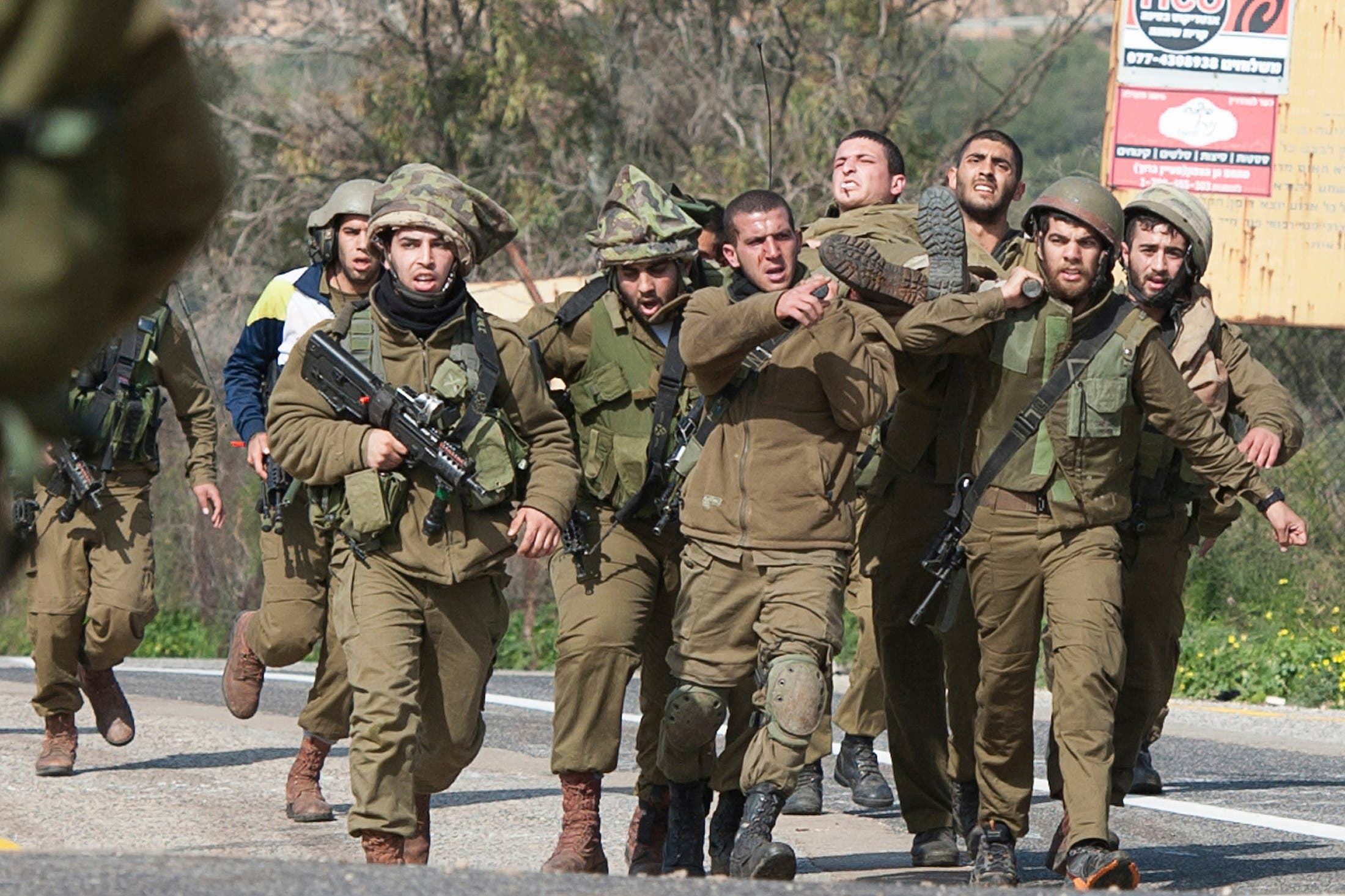 Israeli soldiers carry a wounded comrade on a stretcher near Israel's border with Lebanon January 28, 2015. The threat of a full-blown conflict between Israel and Hezbollah increased on Wednesday after the Lebanese militant group fired a missile at an Israeli army vehicle along the frontier and wounded seven soldiers, the biggest escalation since a 2006 war. REUTERS
