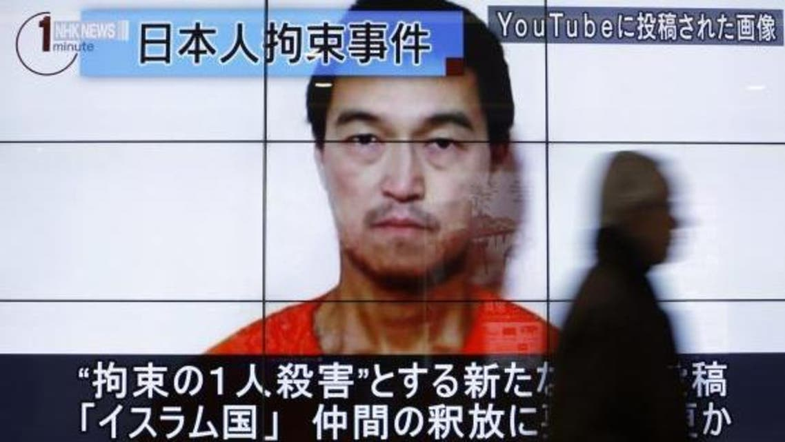 A man walks past screens displaying a television news programme showing an image of Kenji Goto, one of two Japanese citizens taken captive by Islamic State militants, on a street in Tokyo January 25, 2015. Reuters
