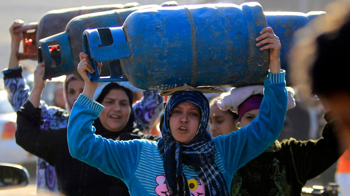 Women carry gas cylinders to fill them at a distribution point in Cairo Jan. 19, 2015.  (Reuters)