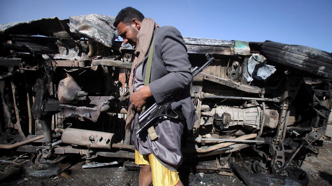A Houthi militant stands next to a destroyed vehicle, which belongs to a Houthi man, after an improvised explosive device under it detonated in Sanaa January 25, 2015. reuters