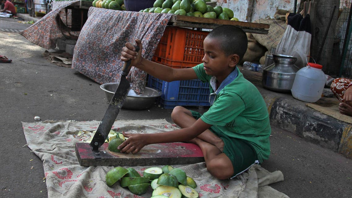 An Indian boy cuts mangoes for sale by a road side as he helps his family in the evening in Ahmadabad, India, Wednesday, June 11, 2014. India recently passed a law aimed at fighting child labor by making education compulsory up to age 14. But grinding poverty still leads many kids to work. Thursday, June 12 marks the World Day against Child Labor. (AP Photo/Ajit Solanki)