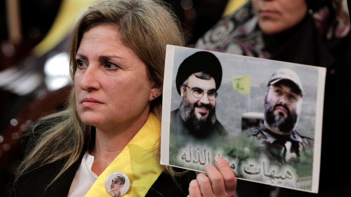 A Hezbollah supporter holds up a portrait of late Hezbollah military commander Imad Mughniyeh, right, and Hezbollah leader Sheikh Hassan Nasrallah, during a ceremony marking the death of six Hezbollah fighters, including the son of Mughniyeh, and an Iranian general who were killed in an Israeli airstrike in Syria's Golan Heights last week, in the southern suburb of Beirut, Lebanon, Friday, Jan. 30, 2015. AP