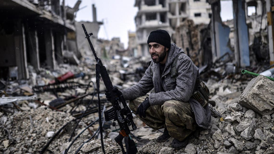 Musa, a 25-year-old Kurdish marksman, sits in the rubble of the Syrian town of Kobane, also known as Ain al-Arab, on January 30, 2015. AFP