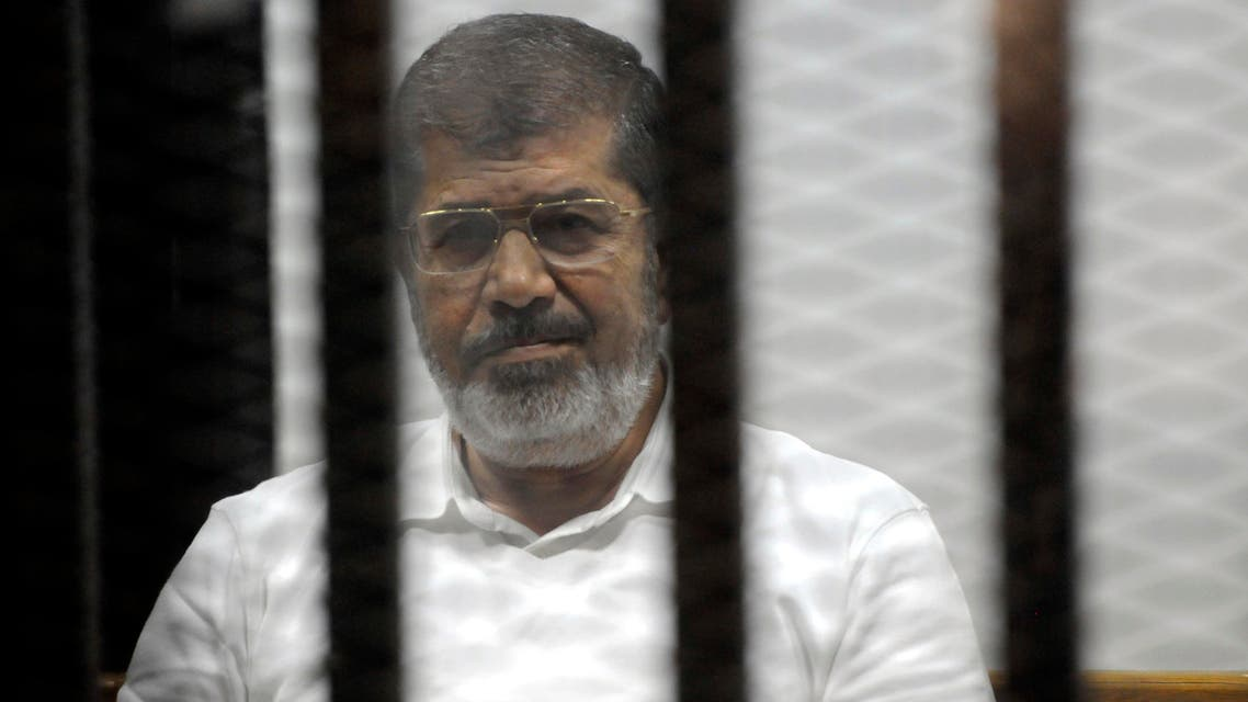 Egypt's ousted Islamist President Mohammed Morsi sits in the defendant cage in the Police Academy courthouse during a court hearing on charges of inciting the murder of his opponents, in Cairo, Egypt, Monday, Nov. 3, 2014. (AP)