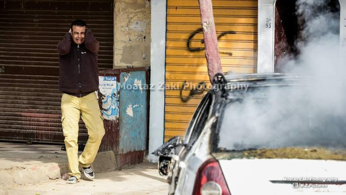 A man, identified by social media users as Mahmoud Abdelaal, reacts as his taxi is torched during confrontations between state forces and protestors. (Photo courtesy: Facebook)