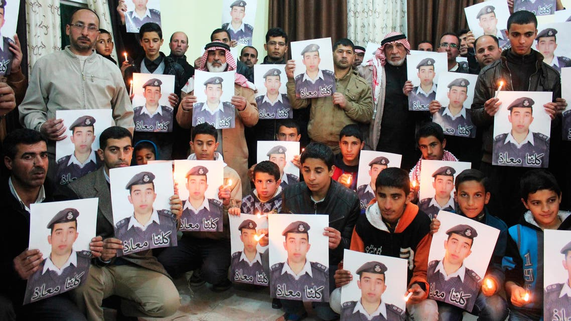 Relatives of ISIS captive Jordanian pilot Muath al-Kasaesbeh hold his portrait as they take part in a rally in his support at the family's headquarters in the city of Karak, January 31, 2015. (Reuters)