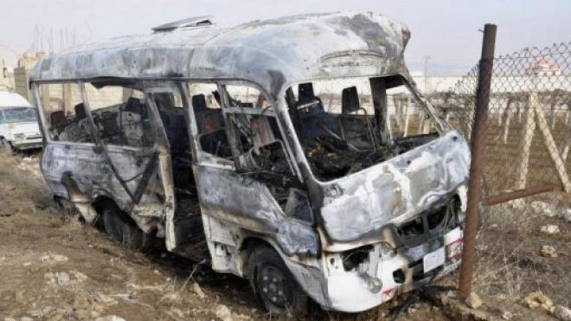 A Syrian Arab News Agency photo shows a burnt bus at the scene of a blast