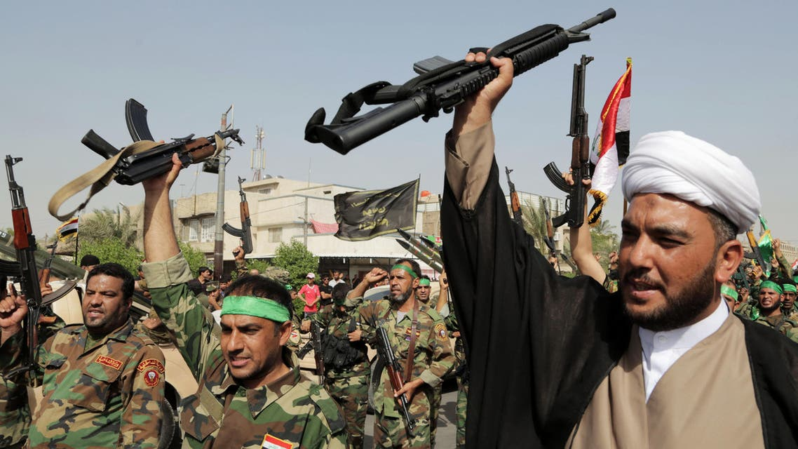 """volunteers of the newly formed """"Peace Brigades"""" raise their weapons and chant slogans against the al-Qaida-inspired Islamic State of Iraq and the Levant during a parade in the Shiite stronghold of Sadr City, Baghdad, Iraq. (AP)"""