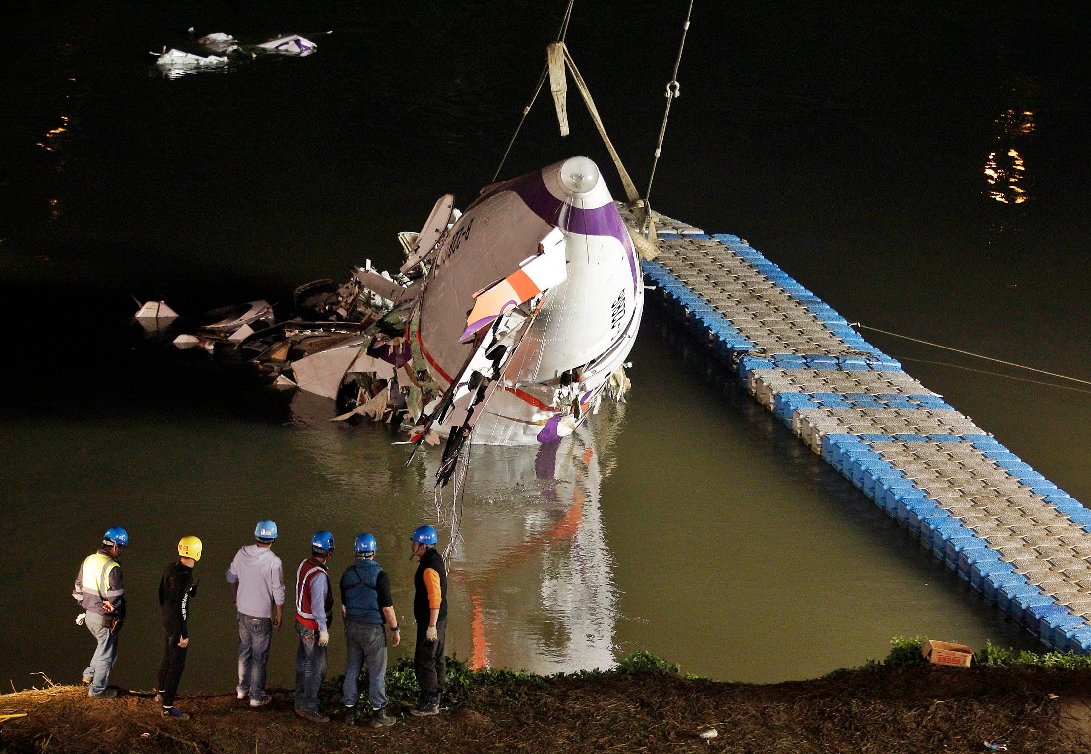 Cranes lift the crashed plane from a Taiwan river (Reuters)