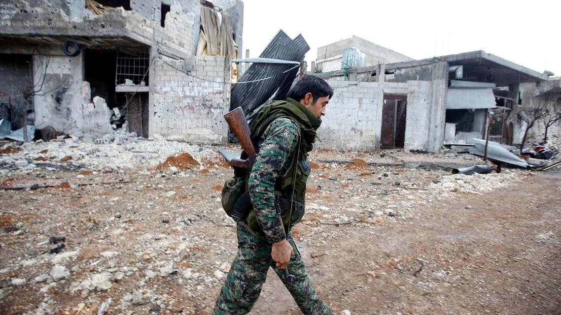 A fighter of the Kurdish People's Protection Units (YPG) walks past damaged buildings in the northern Syrian town of Kobani Jan. 30, 2015.  (Reuters)