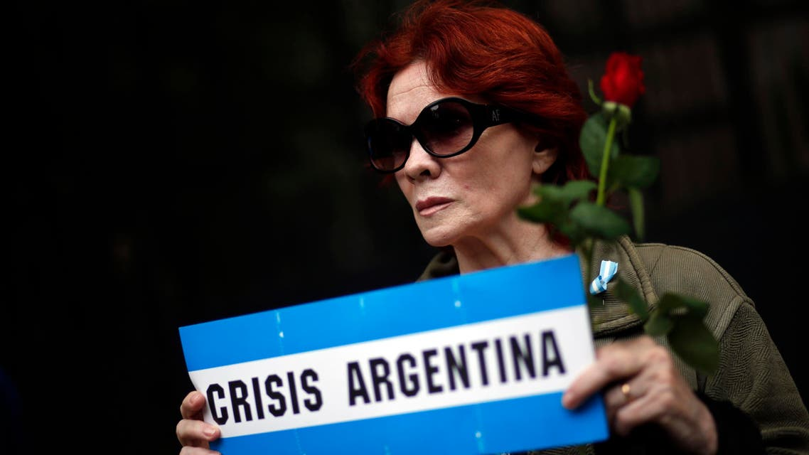 A woman holds a rose and a sign as she stands outside the place where the wake for late state prosecutor Alberto Nisman is being held in Buenos Aires January 28, 2015. (Reuters)