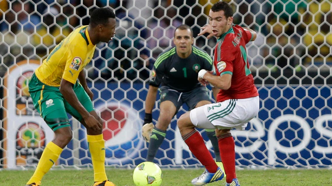 South Africa's Siyabonga Sangweni, left, scores past Morocco's Abderrahim Achchakir, right, and goalkeeper Nadir Lamyaghri in their African Cup of Nations Group A soccer match, in Durban, South Africa, Sunday, Jan. 27, 2013. (AP)
