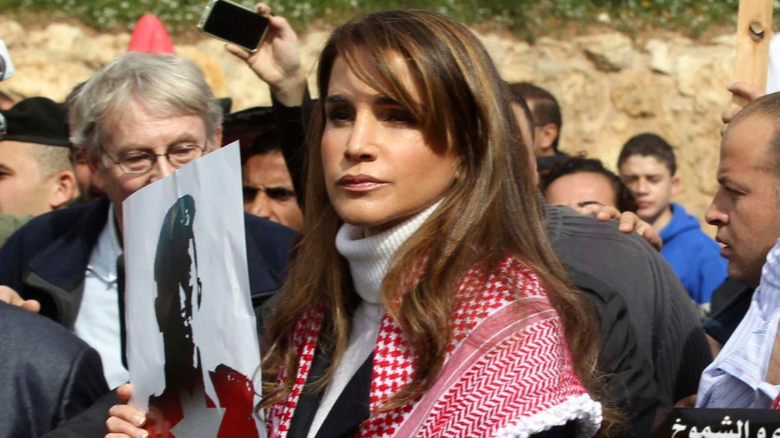"""Jordan's Queen Rania (C) holds a picture of recently executed Jordanian pilot Muath al-Kasasbeh, with the words in Arabic reading """"Muath is a martyr of right"""", during a march after Friday prayers in downtown Amman February 6, 2015. (Reuters)"""