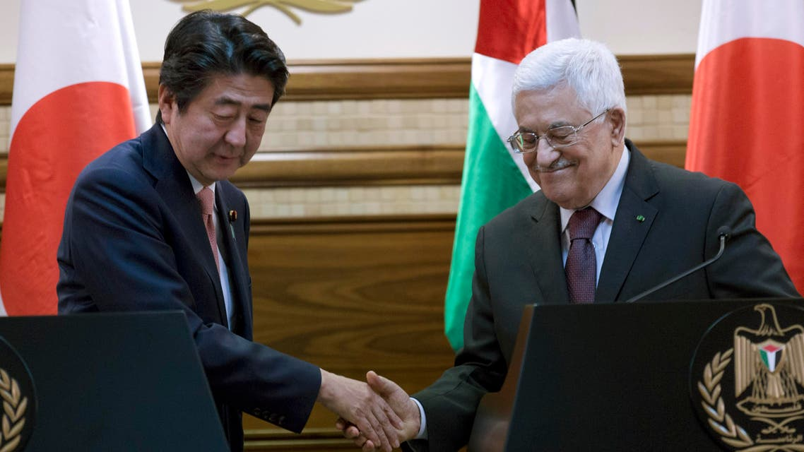 Palestinian President Mahmoud Abbas, right, and Japanese Prime Minister Shinzo Abe shake hands after holding a joint press conference at the Palestinian Authority headquarters, in the West Bank city of Ramallah, Tuesday, Jan. 20, 2015. (AP)