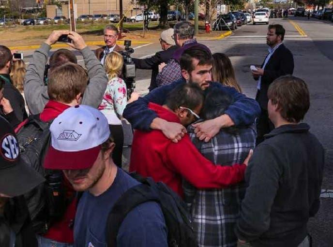 وراح طلابه يعزون بعضهم بعد معرفتهم بما حدث، وخلفهم ظهر المسؤول عن الشرطة طوم بيري