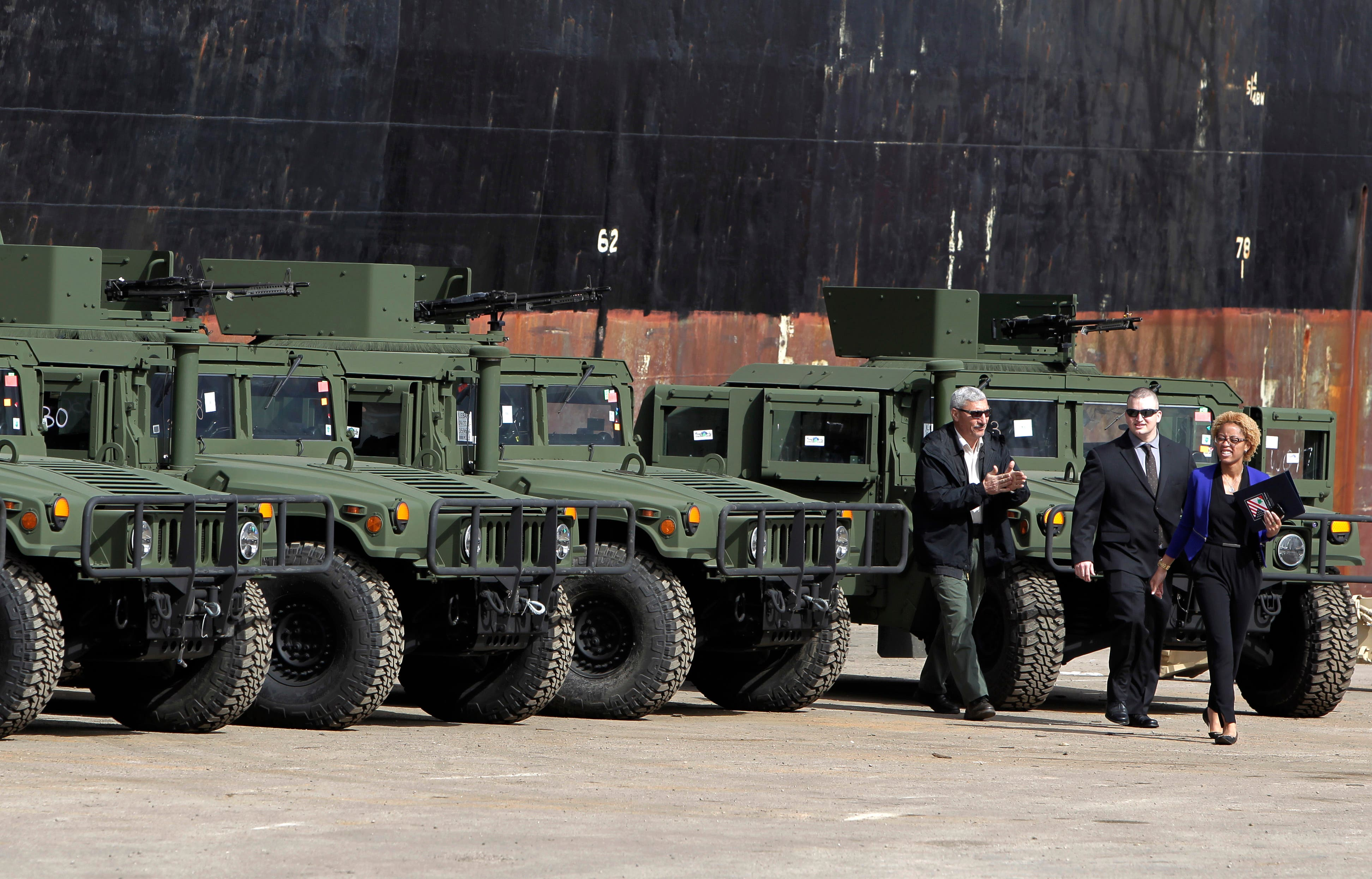 U.S. Embassy employees walk by vehicles that were unloaded from a ship at Beirut's port in Lebanon on Sunday, Feb. 8, 2015.  (AP)
