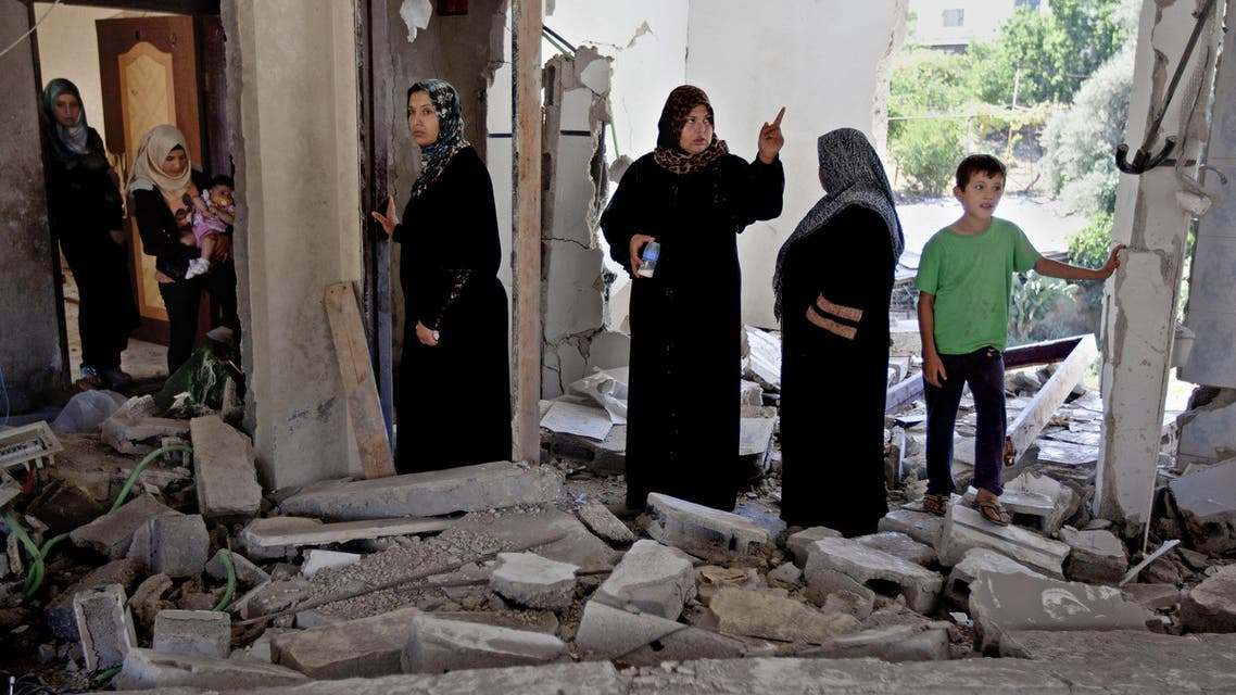 Palestinian women and children inspect the damaged family home of Ziad Awad in the town of Idna, 13 kilometers (8 miles) west of the West Bank city of Hebron, Wednesday, July 2, 2014. (File photo: AP)