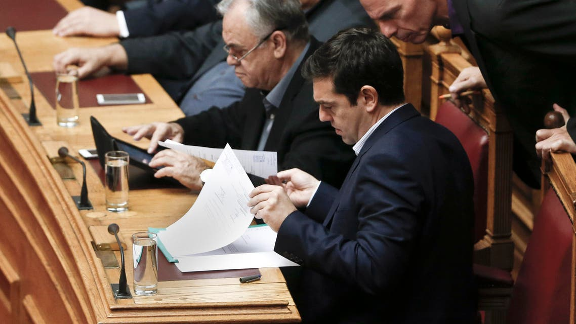 Greek Minister Alexis Tsipras front and his Finance Minister Yanis Varoufakis, right, look on papers during the vote for the president of Greece's parliament in Athens, on Friday, Feb. 6, 2015. (AP)