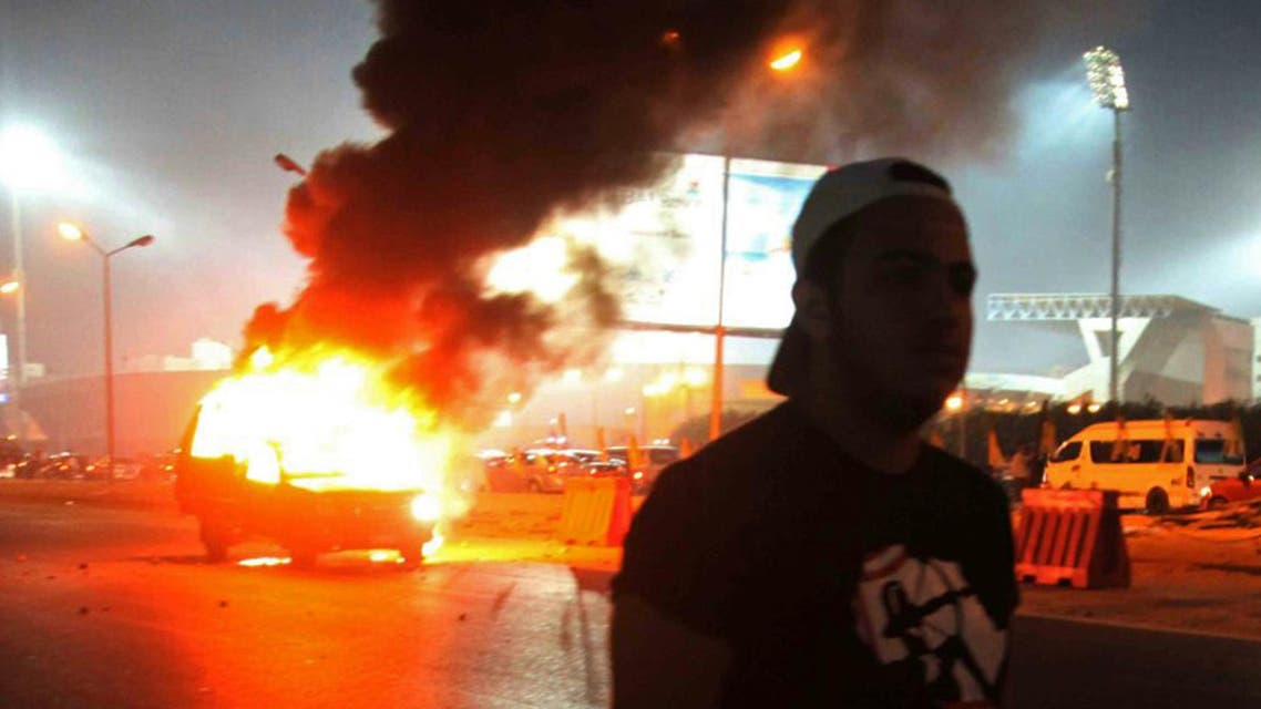A soccer fan is seen near a police car, which was set on fire by fireworks, during clashes between soccer fans and security forces in front of a stadium on the outskirts of Cairo February 8, 2015. (Reuters)